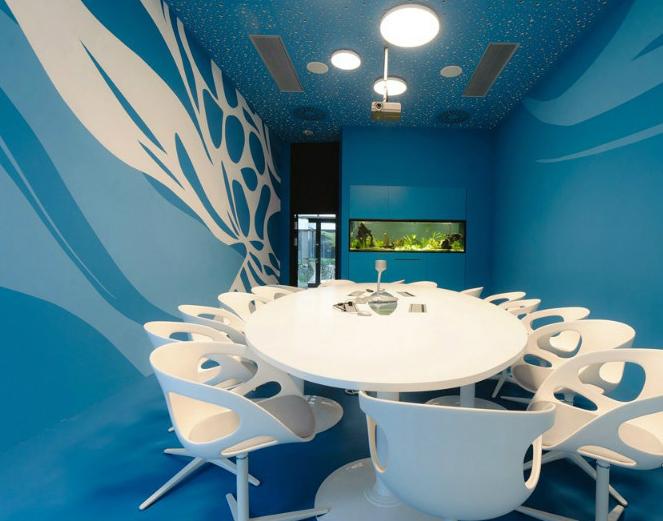 海洋主题色的会议室,搭配着白色的会议桌椅.